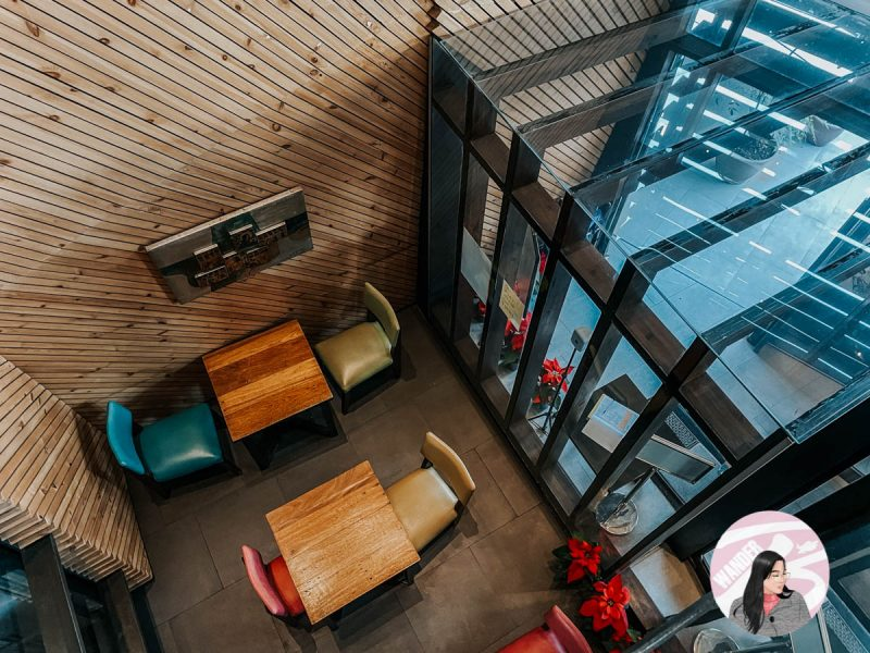 colorful chairs and wooden tables near the glass entrance of g1 lodge design hotel